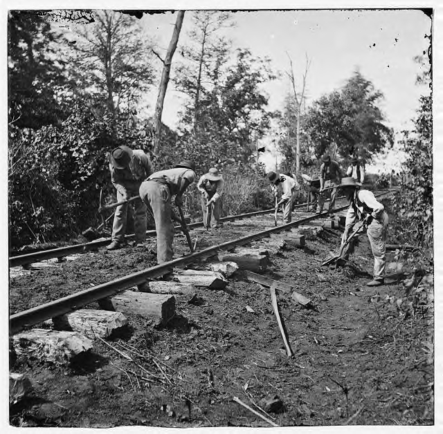 Track maintenance. This is T-rail, with a spike at each tie. Notice that the ties are laid in the dirt.