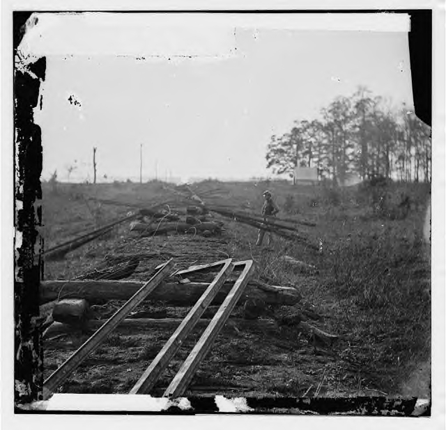 Track destroyed by retreating Confederates on the Orange & Alexandria RR in the spring of 1862. The picture is down the road bed. The rails were bent around a post. There appears to have been no burning of ties or heating of rails here.